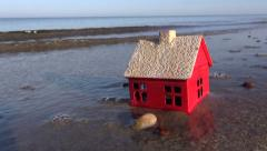 Small model of a house on an ocean beach and waves Stock Footage