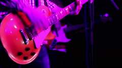 A musician playing red guitar closeup Stock Footage