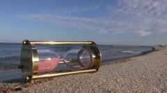 Ancient brass sandglass hourglass on sea beach sand Stock Footage