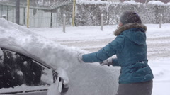 Woman Brushes Snow Off Her Car On A Winter Morning Stock Footage