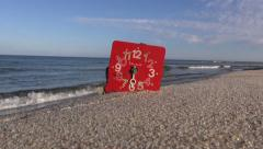 Antique red broken clock face dial on sea resort beach. Time and sea Stock Footage