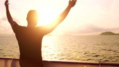 Young Man Spiritual Worship Pose Outstretched  Arms Sun Cruise Ship Water Sunset - stock footage