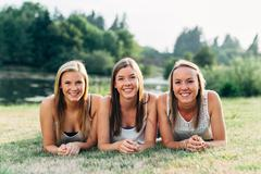 three sisters laying down in grass smiling - stock photo