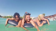 Family lying on inflatable airbed in splashing camera position. slow motion s Stock Footage