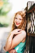 attractive young red head leaning against fence looking at camera laughing sm - stock photo