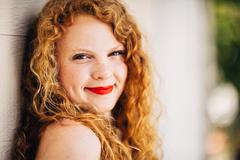 attractive young red head leaning against white wall close up - stock photo
