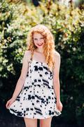 Attractive young red head sun directly overhead playing with dress Stock Photos
