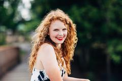 Attractive young red head smiling, leaning over railing Stock Photos