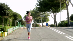 Beautiful girl jogging on street doing sport wide shot Stock Footage