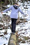 Boy balancing on log in the winter Stock Photos