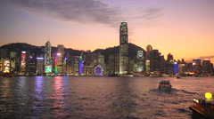 Time Lapse of boats driving along Victoria Harbour in Hong Kong Central at night Stock Footage