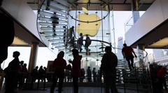 Customers walk on the spiral stairs at an Apple store in Hong Kong's IFC Stock Footage