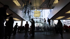 Customers walk on the spiral stairs at an Apple store in Hong Kong's IFC - stock footage