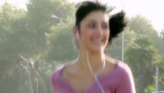 Closeup of gorgeous female model jogging on street happy listening music Stock Footage
