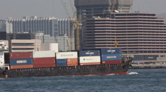 Cargo ship carrying containers drives at Victoria Harbour Stock Footage