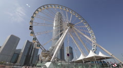 Time Lapse of the Ferris wheel turning near IFC building in Hong Kong Central Stock Footage