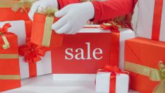 Girl taking out present from heaps of Christmas gift boxes with word Sale - stock footage