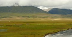 4k clouds mass rolling over Tibet mountain,River flowing the prairie. Stock Footage