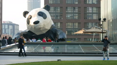Timelapse of people visit the statue of giant panda climbing on a building Stock Footage