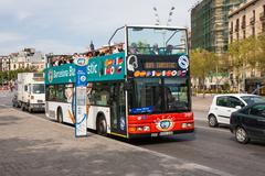Bus stop and sightseeing bus with tourists in barcelona, spain Stock Photos