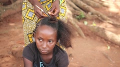 Africa village girl brushing and braiding hair Guinea Bisseau close up Stock Footage