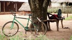 Africa village man resting beside bike Guinea Bisseau Stock Footage