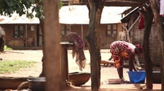 Africa village woman washing and drying dishes Guinea Bisseau Stock Footage