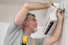 Stock Photo of electrical installation of air conditioner, electrician at work
