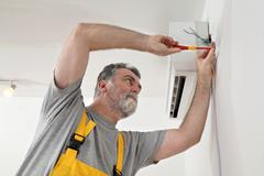 electrical installation of air conditioner, electrician at work - stock photo