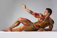 muscular young man with skin painted with holi colors, laying down on the flo - stock photo