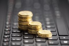 Rising coins on keyboard - stock photo