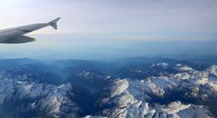 Snow-covered mountain peaks with altitude aircraft. Stock Photos