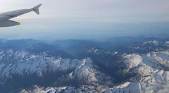 snow-covered mountain peaks with altitude aircraft. - stock photo