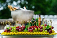 Platter of assorted fresh fruit at buffet table - stock photo