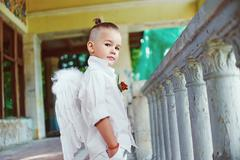 boy with angel wings on old city background - stock photo
