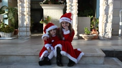 Two girls pose as Santa before they join Christmas Eve parade Stock Footage