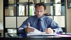 Young businessman reading and analyzing documents sitting at homeHD Stock Footage