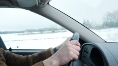 Tense male hands on steering wheel driving car on slippery road in winter time Stock Footage