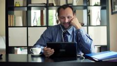 Happy businessman watching movie on tablet computer sitting by desk at home HD Stock Footage