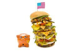 enormous burger falling over on piggy bank - stock photo