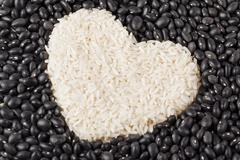 heart shape rice grains isolated on the dark beans - stock photo