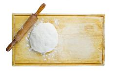 pizza dough and rolling pin on wooden worktop - stock photo