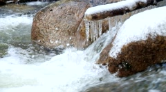 Small icicles glitter above milky blurred water of noisy stream. Stock Footage