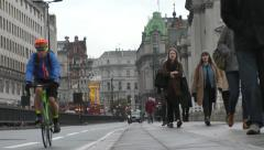 Cyclist on cycle lane and pedestrians on pavement walking Stock Footage