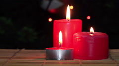 Red Christmas Candles burn against Christmas Tree with Garland Lights Stock Footage