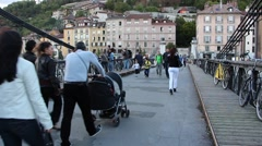 People crossing bridge over the river Isere in Grenoble, France Stock Footage