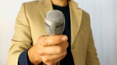 Blurred interviewer holding a microphone over white background Stock Footage