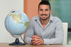handsome young man holding a globe at office - stock photo
