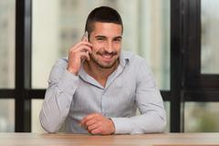 male student talking on the phone in library - stock photo