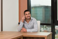 Male student talking on the phone in library Stock Photos